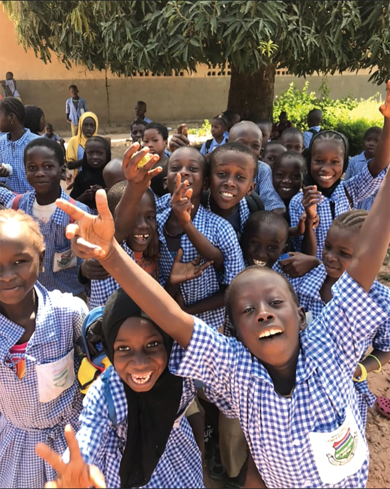 Glada barn på skolrast utanför sin skola i Gambia